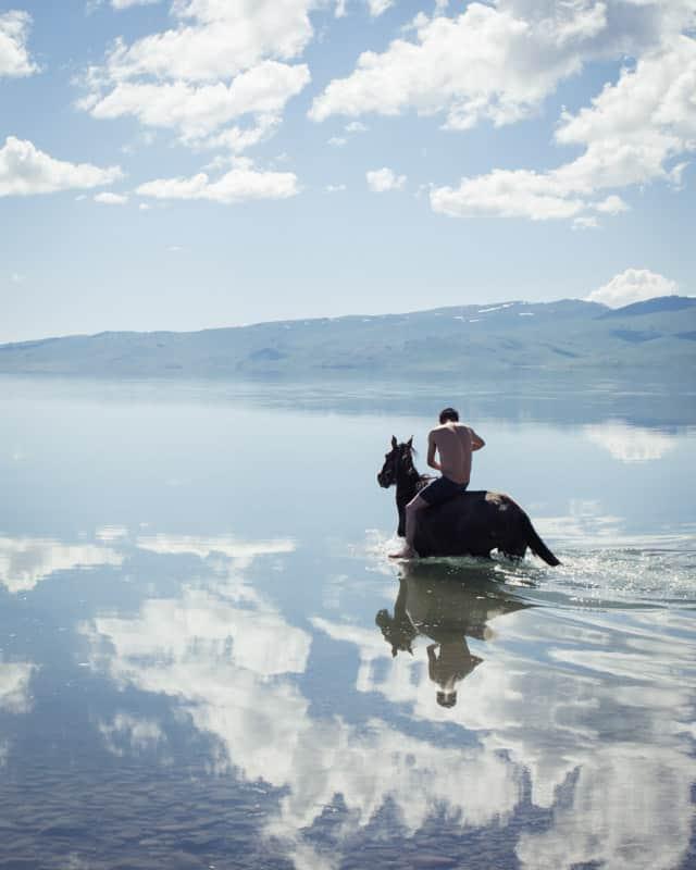 Baignade dans le lac Song Kul avec le dresseur et son cheval