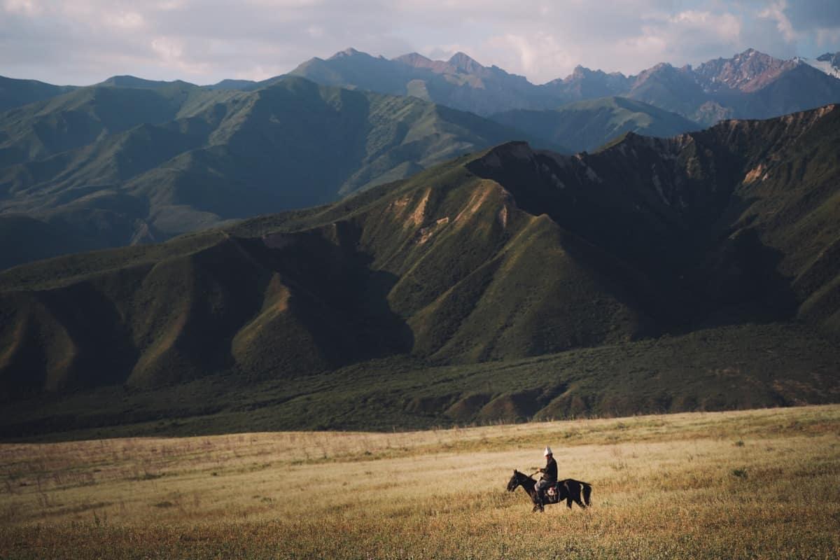cavalier kirghize sur son cheval dans une plaine du Kirghizistan